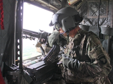A U.S. Army crew chief scans his sector from a CH-47 Chinook helicopter in Afghanistan, May 8, 2015