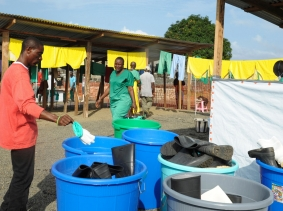Medicins Sans Frontieres health workers disinfect protection clothes and boots outside the isolation unit at ELWA hospital in Monrovia August 23, 2014, photo by 2Tango/Reuters