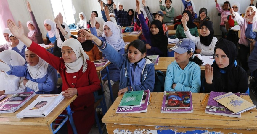 Syrian refugee students raise their hands as they attend class in a UNICEF school at the Al Zaatari refugee camp, Jordan, March 11, 2015