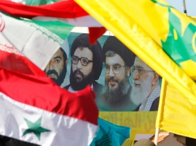 A poster of Ayatollah Ali Khamenei, Hezbollah Secretary-General Sayyed Hassan Nasrallah, and others behind Iranian, Syrian, Lebanese, and Hezbollah flags during Resistance and Liberation Day celebrations in Bint Jbeil, Lebanon, May 25, 2014, photo by Ali Hashisho/Reuters