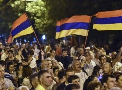 Protesters wave Armenian national flags during a rally against a hike in electricity prices in Yerevan, Armenia July 1, 2015
