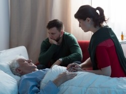 An elderly man in a hospital bed visits with his family