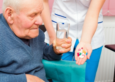 Nurse handing medications to a senior man