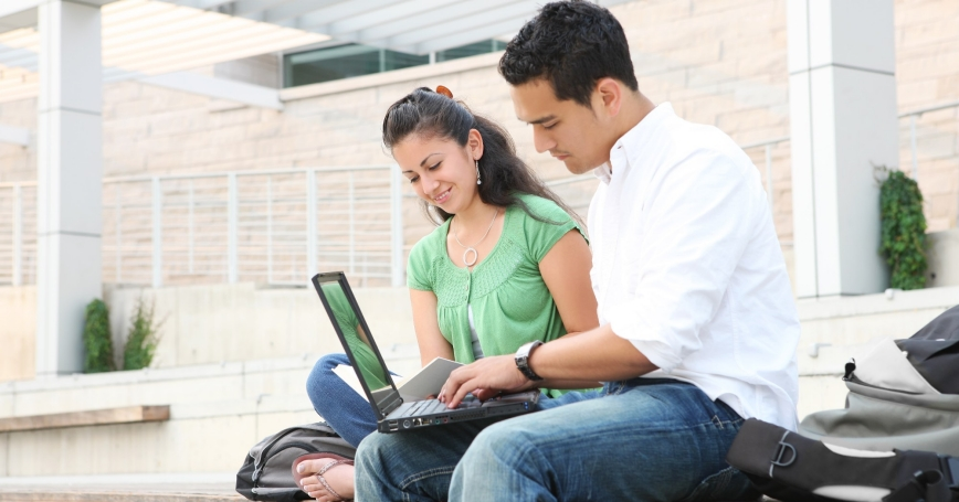 Two college students sitting outside using a laptop