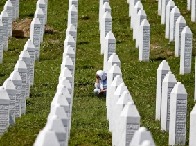 A woman grieves near the grave of a relative who was a victim of the 1995 Srebrenica massacre, at the Potocari Memorial Center and Cemetery, Bosnia and Herzegovina