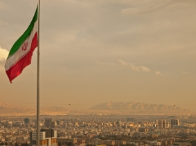 Iran flag above Tehran skyline, photo by Borna_Mir/Fotolia