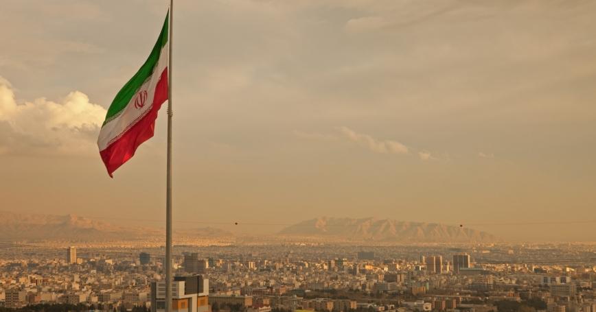 Iran flag above Tehran skyline