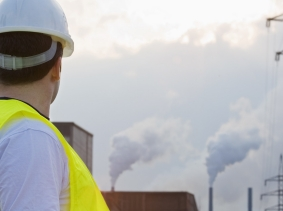 Engineer looking at factory emissions, photo by Darren Baker/Fotolia