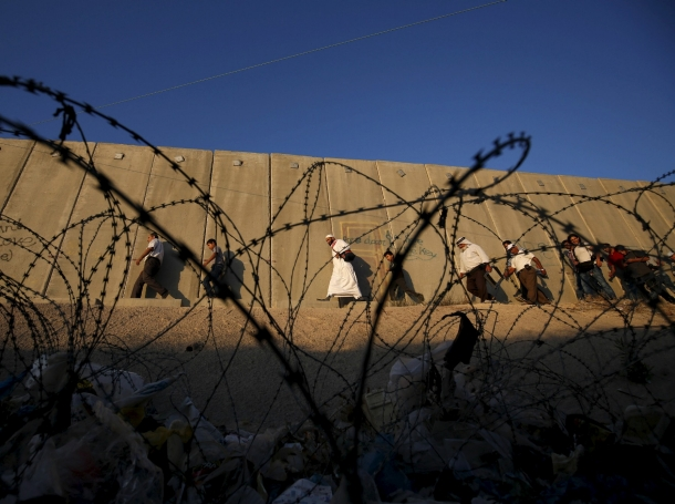Palestinians walk past Israel's controversial barrier at a checkpoint near Ramallah, July 10, 2015
