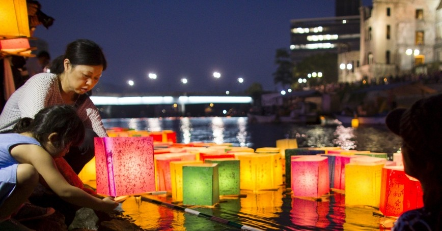 A woman and child release lanterns into the Motoyasu River on the 70th anniversary of the bombing of Hiroshima, Japan, August 6, 2015