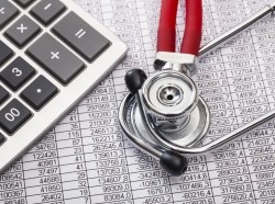 Calculator and stethoscope on a spreadsheet