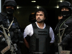 Argentine policemen escort Henry de Jesus Lopez Londono, alleged leader of a Colombian drug trafficking group, outside a courthouse in Buenos Aires October 31, 2012, photo by Stringer/Reuters