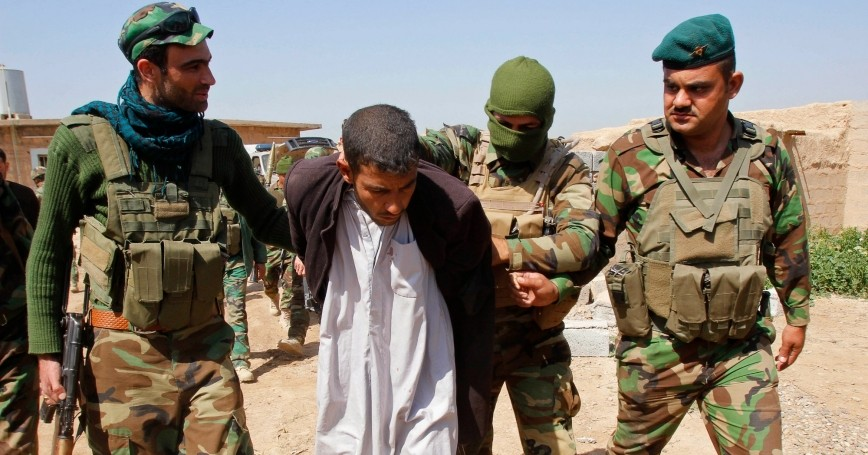 Members of the Kurdish peshmerga forces detain a man suspected of having links to the Islamic State, on the outskirts of Kirkuk March 15, 2015