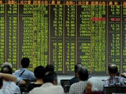 Investors watch stock information at a brokerage house in Hangzhou, Zhejiang province, August 25, 2015
