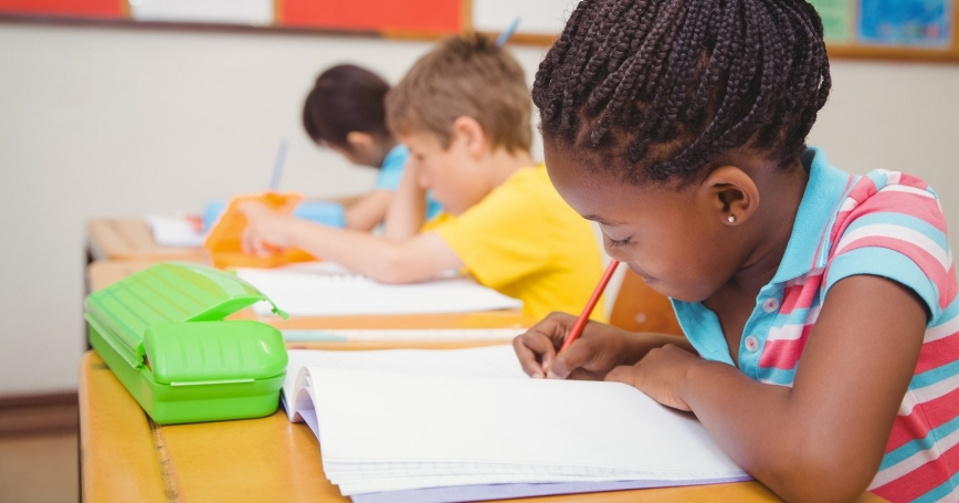 Pupils writing at desk in classroom