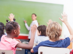 Children raise their hands in a classroom