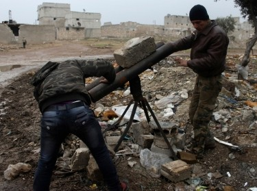 Rebel fighters in Syria prepare a mortar to be launched