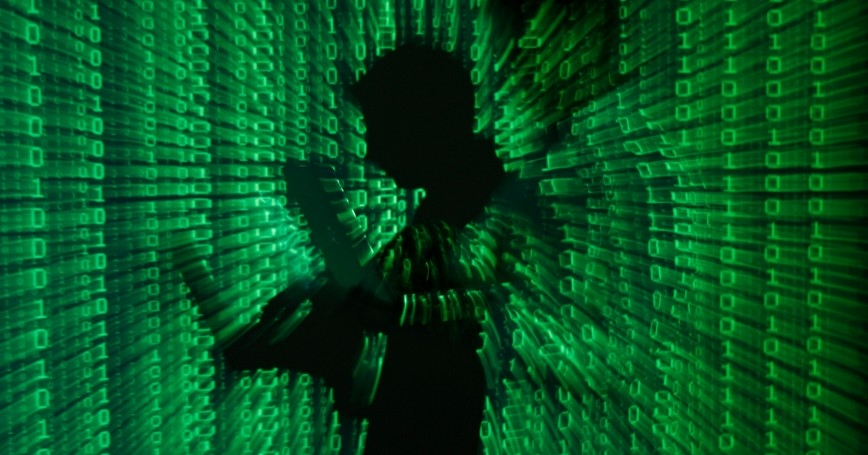 An illustration of a projection of binary code on a man holding a laptop computer