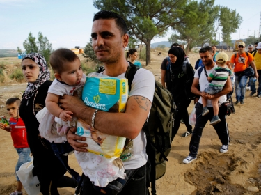 Syrian refugees walk towards a crossing point at Greece's border with Macedonia, September 8, 2015