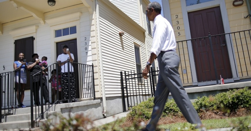 Local residents take pictures as U.S. President Barack Obama visit an area reconstructed after Hurricane Katrina during a presidential visit to New Orleans, Louisiana, August 27, 2015