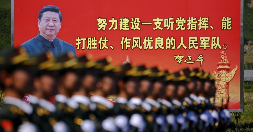 A billboard of Chinese President Xi Jinping is seen behind soldiers of the People's Liberation Army at a military base in Beijing, August 22, 2015