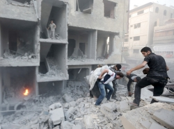 Men search for survivors at a site hit by shelling in Damascus, Syria, June 16, 2015