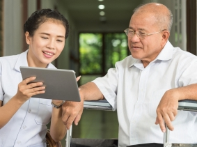 Woman using a digital tablet with an elderly man, photo by Ratthaphon Bunmi/Fotolia