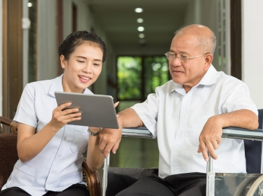 Woman using a digital tablet with an elderly man