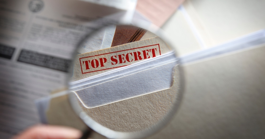A person looking at top secret files with a magnifying glass