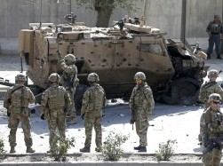 NATO soldiers near a damaged NATO military vehicle at the site of a suicide car bomb blast in Kabul, Afghanistan, October 11, 2015
