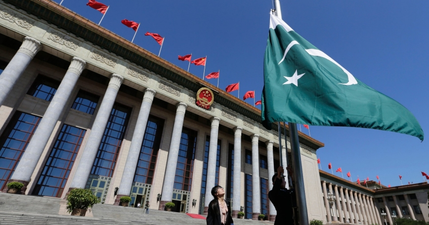 Staff raise Pakistan's flag in front of the Great Hall of the People ahead of a welcome ceremony for Pakistan's Prime Minister Nawaz Sharif in Beijing, July 5, 2013