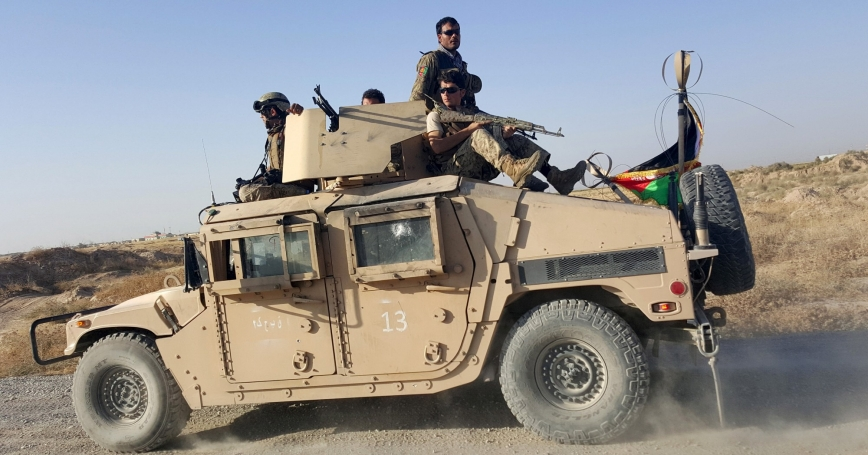 Afghan security forces sit on top of a vehicle as they patrol outside of Kunduz city, October 1, 2015