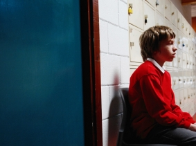 A young student sitting outside in a school corridor, photo by AlbanyPictures/iStock