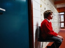 A young student sitting outside in a school corridor