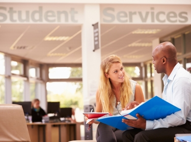 College student discussing assignment with tutor