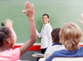 Elementary students raising their hands in class