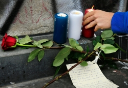 Candles in the French national colours are placed near the Bataclan concert hall the morning after a series of deadly attacks in Paris, November 14, 2015