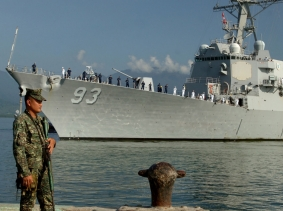 An Armed Forces of the Philippines marine sentry stands watch as the guided-missile destroyer USS Chung-Hoon arrives in Puerto Princesa to participate in Cooperation Afloat Readiness and Training, photo by MC1 Robert Clowney/U.S. Navy