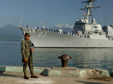 An Armed Forces of the Philippines marine sentry stands watch as the guided-missile destroyer USS Chung-Hoon arrives in Puerto Princesa to participa
