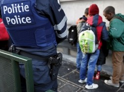 A Belgian police officer stands guard outside a school in central Brussels, November 25, 2015