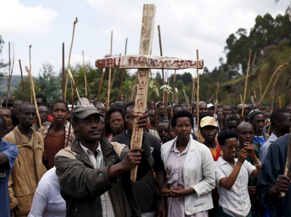 """A man holds a cross that reads """"death to the president"""" as he marches with other protesters who are against Burundi President Pierre Nkurunziza and his bid for a third term, June 3, 2015"""
