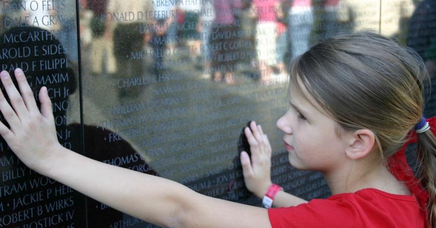 A young girl touches the Vietnam Veterans Memorial in Washington, DC