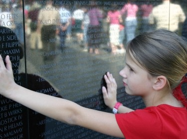 A young girl touches the Vietnam Veterans Memorial in Washington, DC