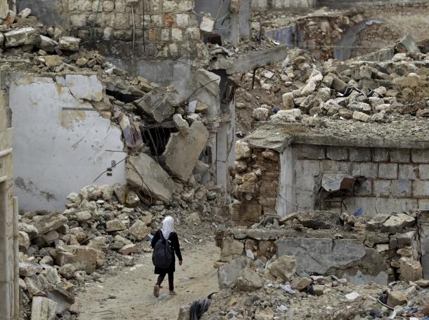 A schoolgirl walks past damaged buildings in Maarrat al-Numan, Syria, October 28, 2015