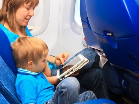 Mother and son using a touch pad tablet on a plane, photo by nadezhda1906/Fotolia
