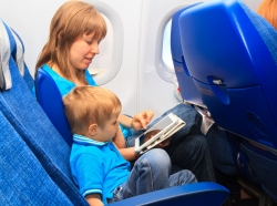Mother and son using a touch pad tablet on a plane