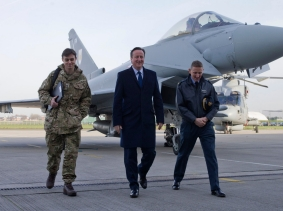 Britain's Prime Minister David Cameron (C) walks with Group Captain David Manning (R) past an RAF Eurofighter Typhoon fighter jet at Royal Air Force station RAF Northolt in London, November 23, 2015, photo by Justin Tallis/Pool/Reuters