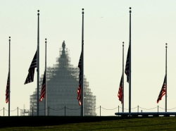 The dome of the U.S. Capitol is seen as flags fly at half staff at the Washington Monument, November 16, 2015