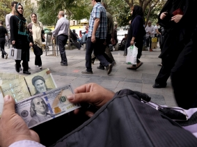A money changer displays U.S. and Iranian banknotes at the Grand Bazaar in central Tehran, October 7, 2015, photo by Raheb Homavandi/Reuters/TIMA