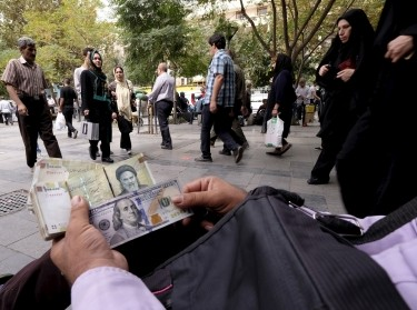 A money changer displays U.S. and Iranian banknotes at the Grand Bazaar in central Tehran, October 7, 2015